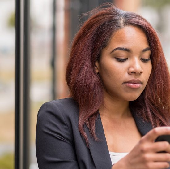 young Black woman plugged into her cell phone