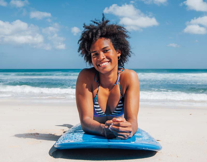 Black woman on the beach with natual hair swimming salt water