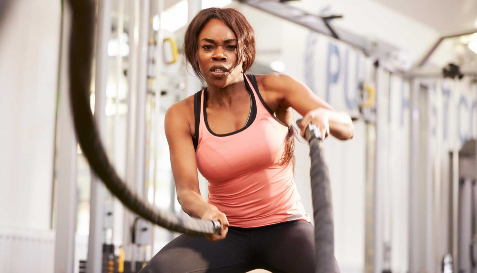 Black woman sweating in the gym exercising with battle ropes