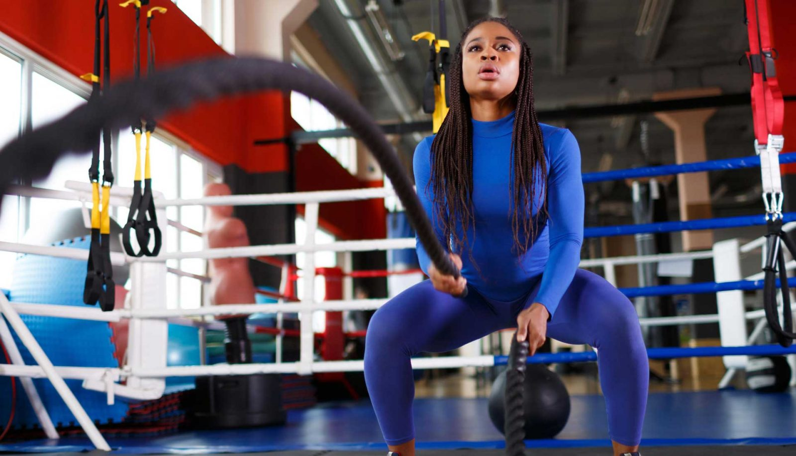 Black woman with braids exercising in the gym with battle ropes