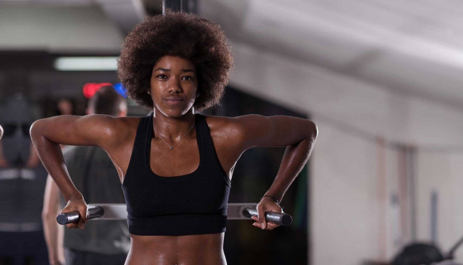 Black woman with natural hair exercising on dip station