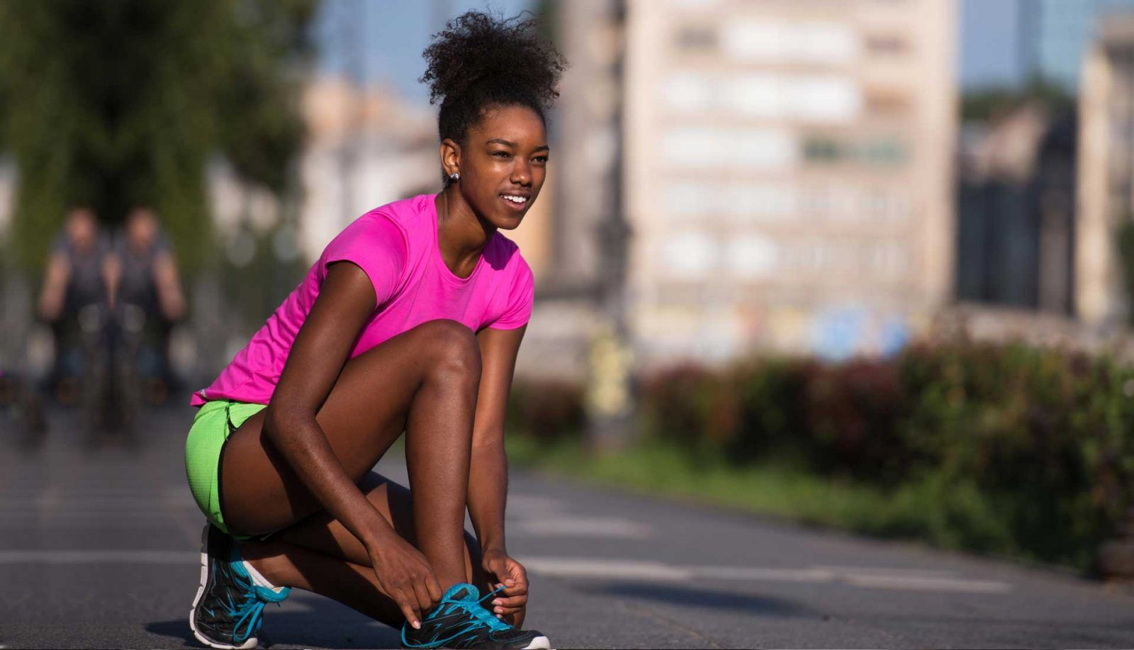Black woman with natural protective hairstyle preparing for a run