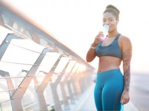 black woman drinking water after exercising